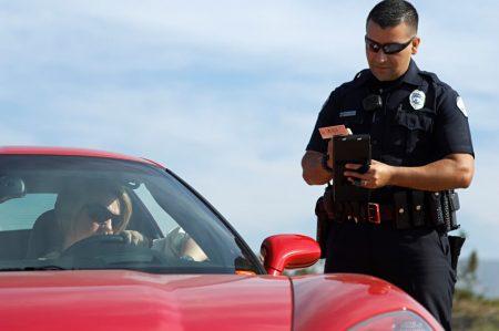 שוטר נותן דוח תנועה לאיש עם רכב אדום